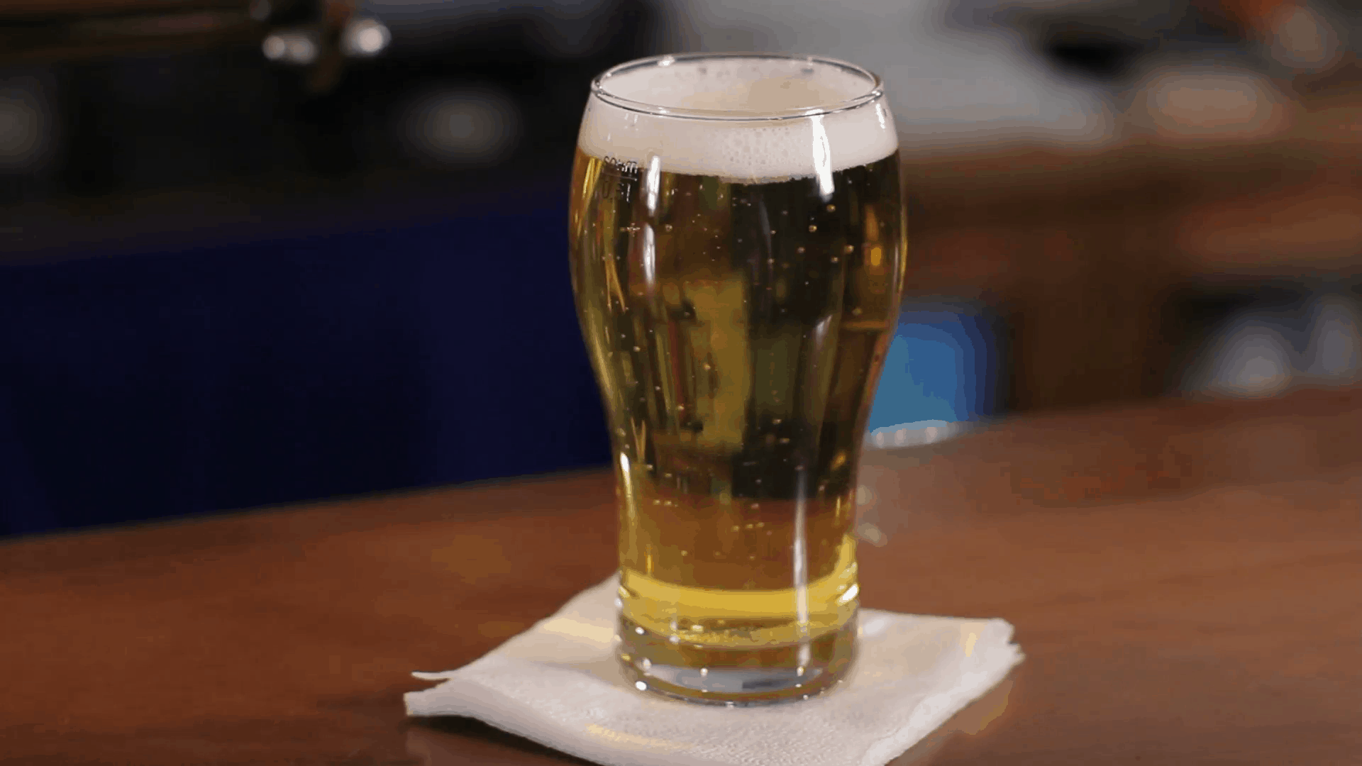 glass-of-beer-on-wooden-bar-counter-close-up-shot_sunpes8v__F0000