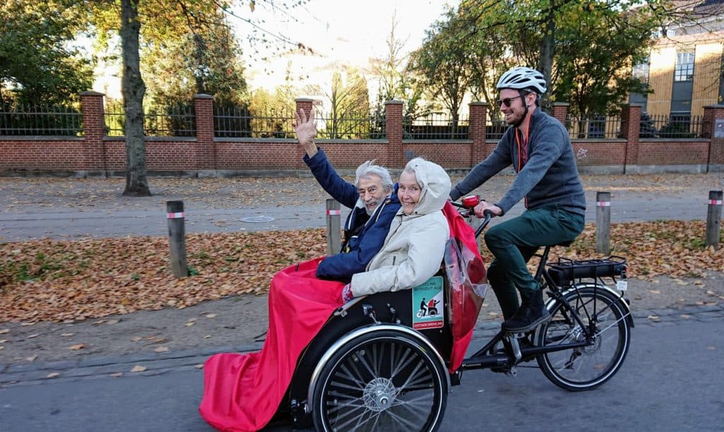 Voluntarios llevan a personas mayores a andar en bici para que no olviden la emoción de sentir el viento en la cara