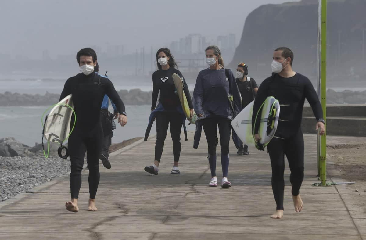 Con mascarillas para protegerse del coronavirus, varios surfistas llegan el jueves 11 de julio de 2020 a la playa reabierta de Waikiki en el distrito de Miraflores, en Lima, Perú. (AP Foto/Martín Mejía)