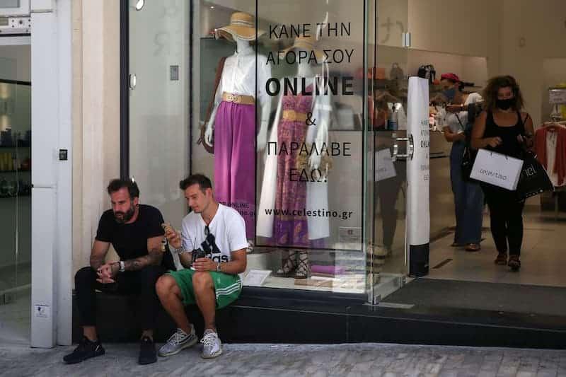 Personas Afuera De Un Comercio, Sin Mascarilla, Y Una Mujer Dentro Del Comercio, Con Mascarilla, En Grecia