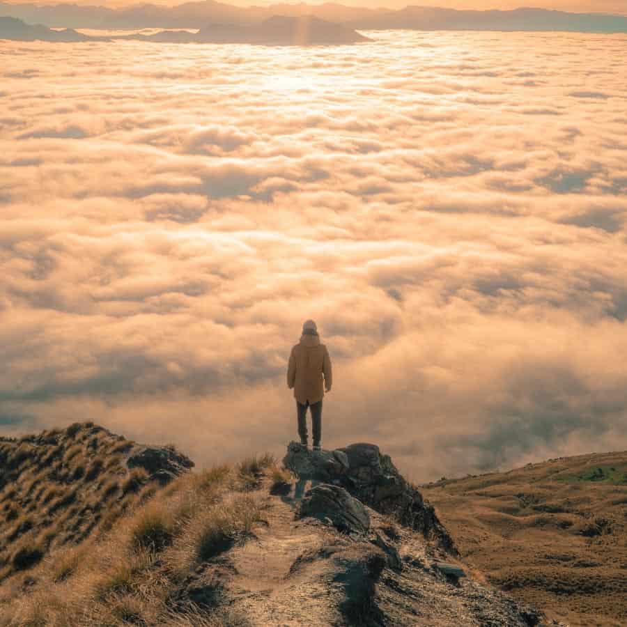 Persona En La Cima De Una Montaña Por Encima De Las Nubes